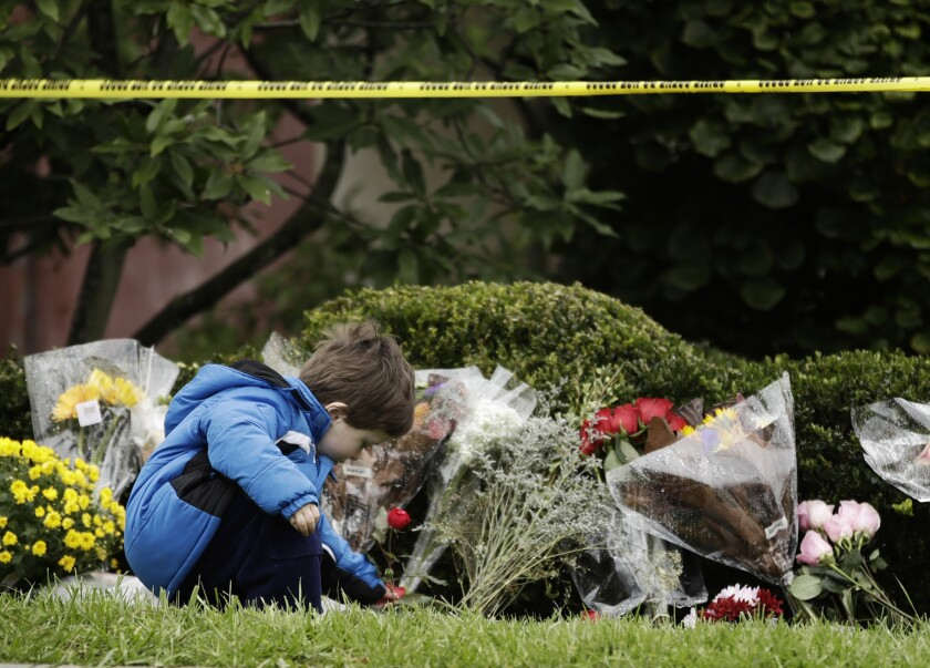 A child places a flower at the Tree of Life synagogue in Pittsburgh on Sunday.
