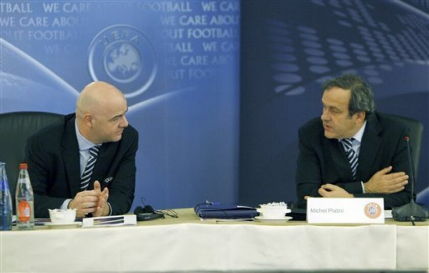 UEFA general secretary Gianni Infantino, left, listens to French UEFA president Michel Platini prior to the UEFA executive meeting in Paris, Monday March, 21 2011. The UEFA will elect its president and renew its executive committee Tuesday. (AP Photo/Jacques Brinon)