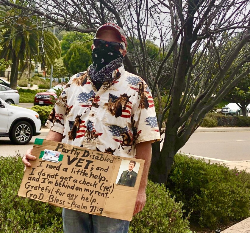 This pandhandler at an intersection in La Jolla wears a mask in keeping with COVID-19 guidelines.