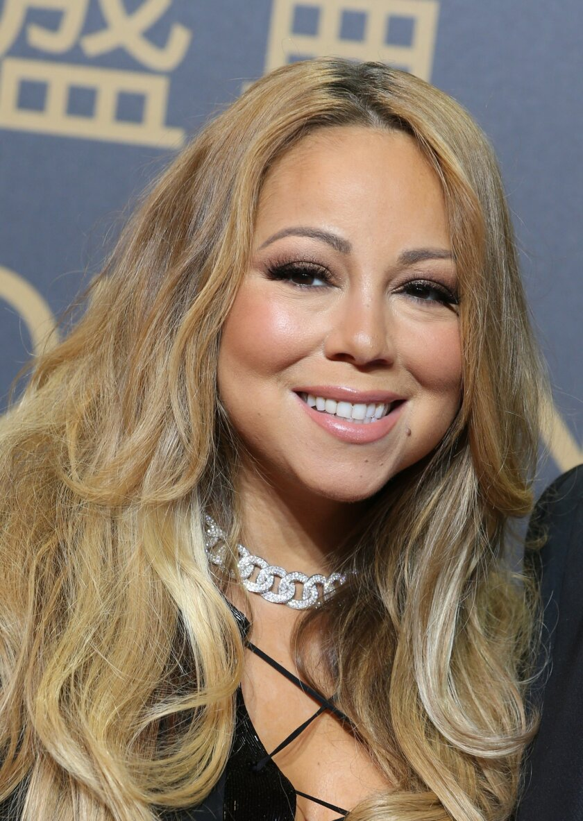 """FILE - In a Tuesday, Oct. 27, 2015 file photo, singer Mariah Carey poses on the red carpet of the opening ceremony for the Studio City project in Macau. Macy's announced Monday, Nov. 2, 2015 that Carey, Questlove from the Roots, the cast of """"Sesame Street,"""" Pat Benatar and Neil Giraldo will be amon"""