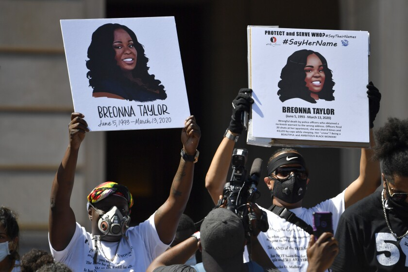 Protesters hold signs showing Breonna Taylor during a rally in her honor at the Kentucky state Capitol in Frankfort.