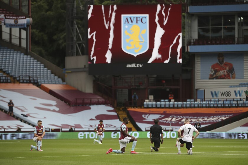 Players kneel prior to the start of the English Premier League soccer match between Aston Villa and Sheffield United at Villa Park in Birmingham, England, Wednesday, June 17, 2020. The English Premier League resumes Wednesday after its three-month suspension because of the coronavirus outbreak. (Carl Recine/Pool via AP)