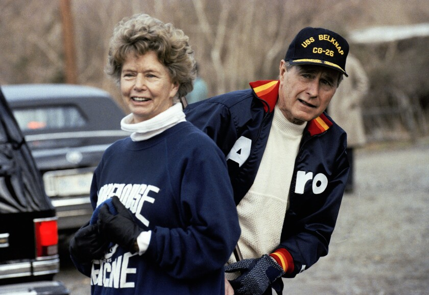 FILE — This Jan. 7, 1990, file photo shows President George H. W. Bush hiding behind his sister, Nancy Ellis, as he prepares for a jog along the C&O canal in the Georgetown section of Washington. A longtime Democrat who helped her Republican brother and nephew get elected president, died of complications of the coronavirus Sunday, Jan. 10, 2021, at an assisted living facility in Concord, Massachusetts. She was 94. (AP Photo/Marcy Nighswander, File)