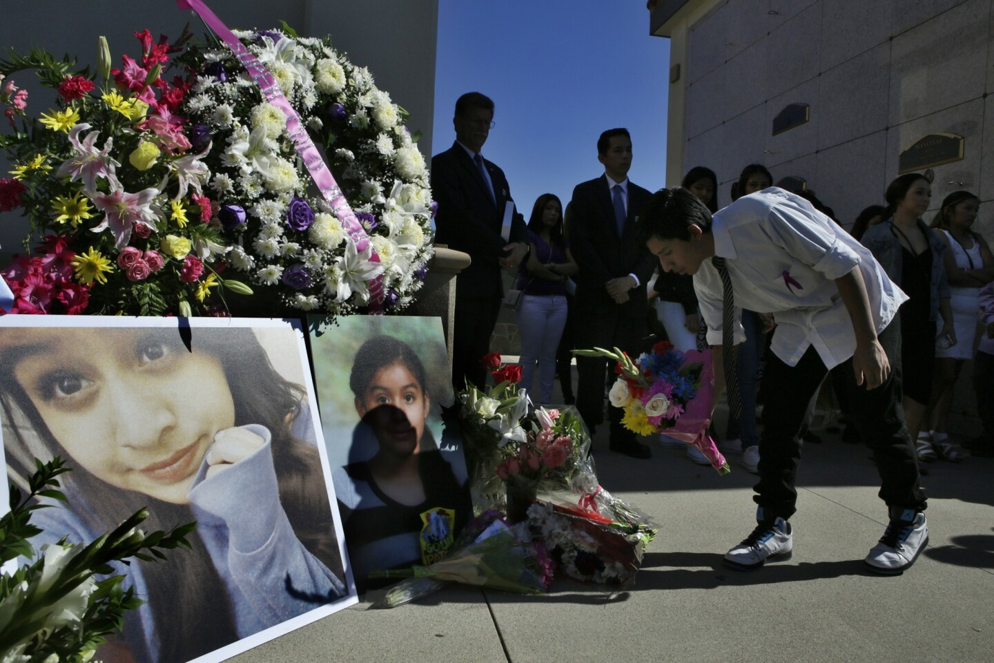 A friend leaves flowers at the service for 13-year-old Andrea Gonzalez at Fairhaven Memorial Park and Mortuary on Saturday in Santa Ana.