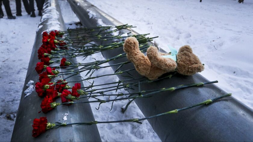 A toy and flowers lie at the scene of a collapsed apartment building in Magnitogorsk, a city of 400,