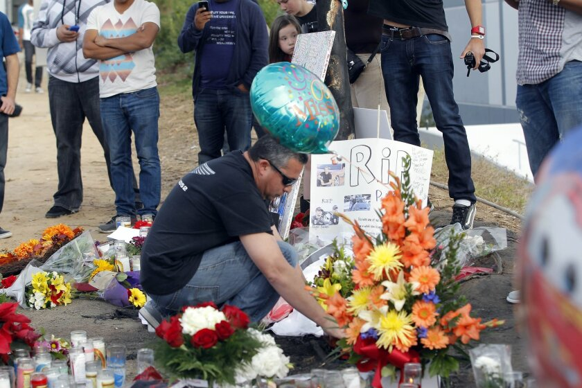 """A man views flowers and memorials at a roadside memorial at the site of the auto crash that took the life of actor Paul Walker and another man, in the small community of Valencia, Calif., Monday, Dec. 2, 2013. The neighborhood where """"Fast & Furious"""" star Walker died in the one-car crash is known to attract street racers, according to law enforcement officials. Walker and his friend and fellow fast-car enthusiast Roger Rodas died Saturday when the 2005 Porsche Carrera GT they were traveling in smashed into a light pole and tree. The two had taken what was expected to be a brief drive away from a charity fundraiser at Rodas' custom car shop in the Southern California community of Valencia, about 30 miles (48 kilometers) northwest of Los Angeles. (AP Photo/Nick Ut)"""