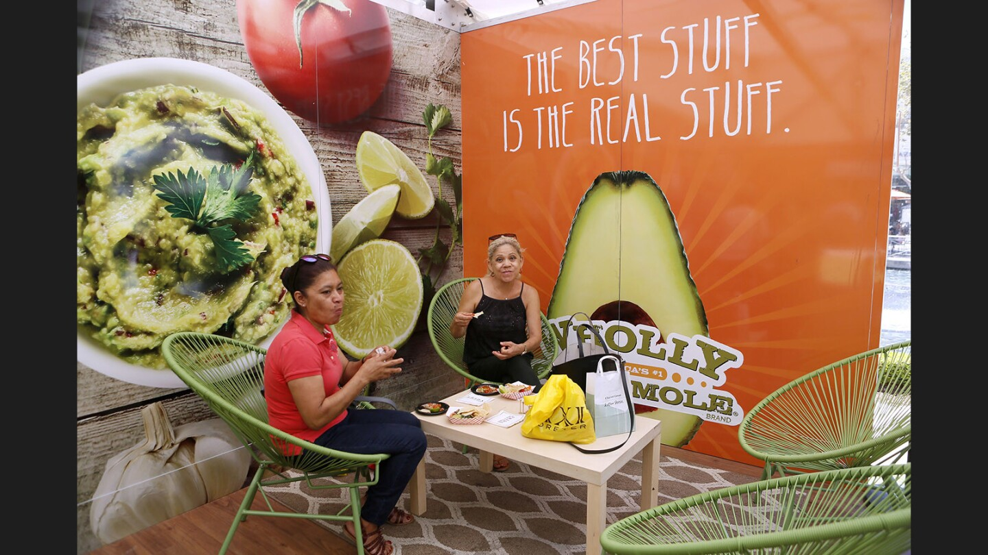Sisters Dina Sanchez, left, and Edith Sanchez, right, enjoy free guacamole, chips and a taco at the Wholly Guacamole Guac Stop pop up restaurant at the Americana at Brand in Glendale on Friday, July 28, 2017.