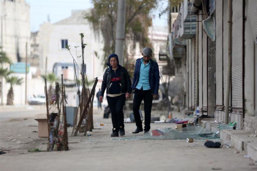 Un hombre y una mujer caminan por una calle de Afrín, Siria, el 19 de marzo del 2018. El presidente de Turquía, Recep Tayyip Erdogan, anunció hoy que su operación contra las fuerzas kurdas no terminará con la toma de la ciudad siria de Afrín, sino que continuará por todo el norte de Siria e incluso en Irak. EFE