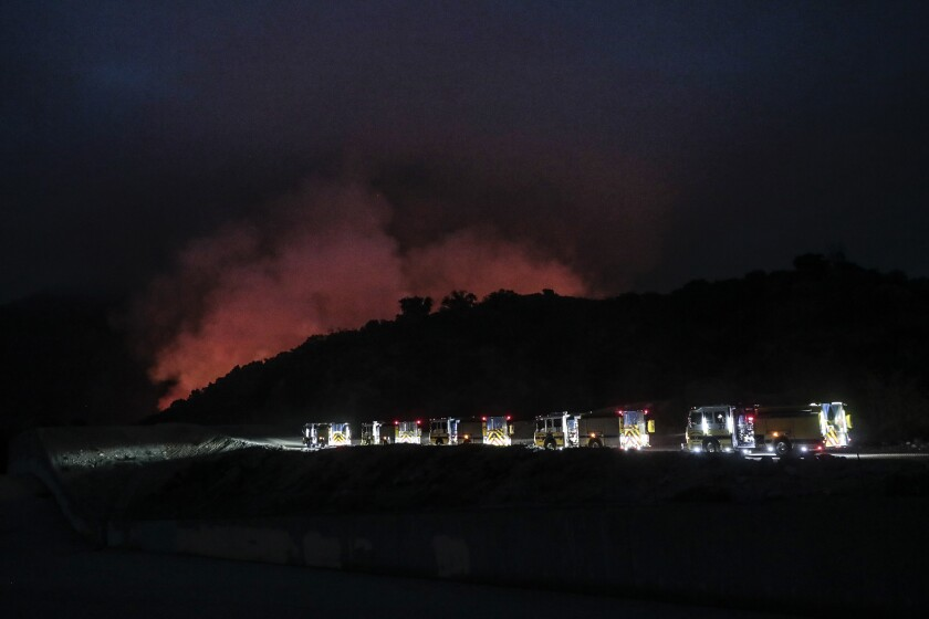 A line of fire engines head to the flaming Santa Anita Canyon as the Bobcat fire burns near Arcadia.