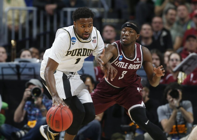 Purdue guard Johnny Hill, left, fights off a potential steal by Arkansas Little Rock guard Josh Hagins in the first half of a first-round men's college basketball game Thursday, March 17, 2016, in the NCAA Tournament in Denver. (AP Photo/David Zalubowski)