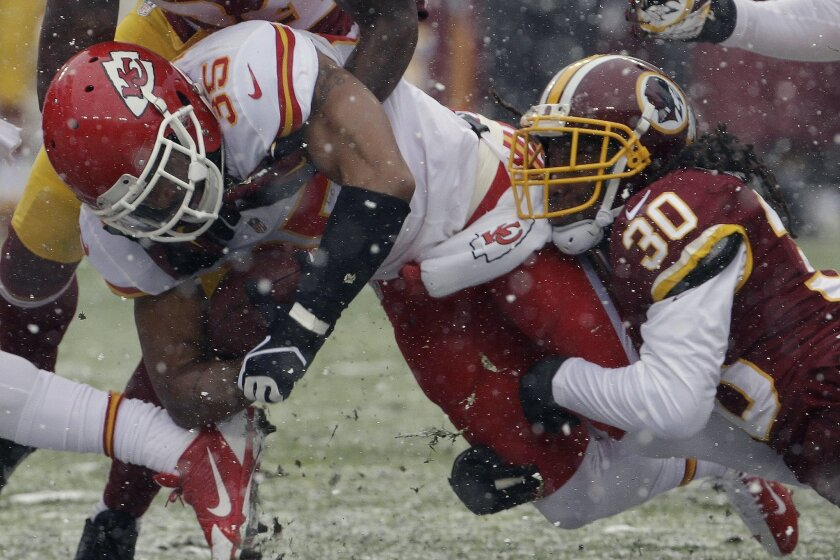 Kansas City Chiefs defensive back Quintin Demps (35) is stopped by Washington Redskins free safety E.J. Biggers (30) during the first half of an NFL football game in Landover, Md., Sunday, Dec. 8, 2013. (AP Photo/Pablo Martinez Monsivais)