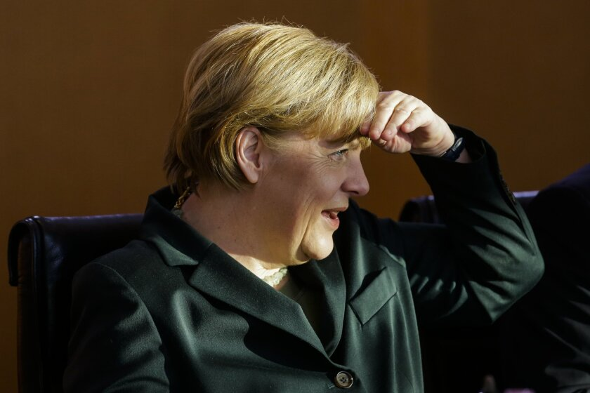German Chancellor Angela Merkel protects her eyes from the sun as she arrives to lead the cabinet meeting at the chancellery in Berlin, Wednesday, Jan. 8, 2014. German Chancellor Angela Merkel suffered a pelvis injury during ski holidays in the Swiss Alps and will have to cut back on her work schedule for the next three weeks. (AP Photo/Markus Schreiber)