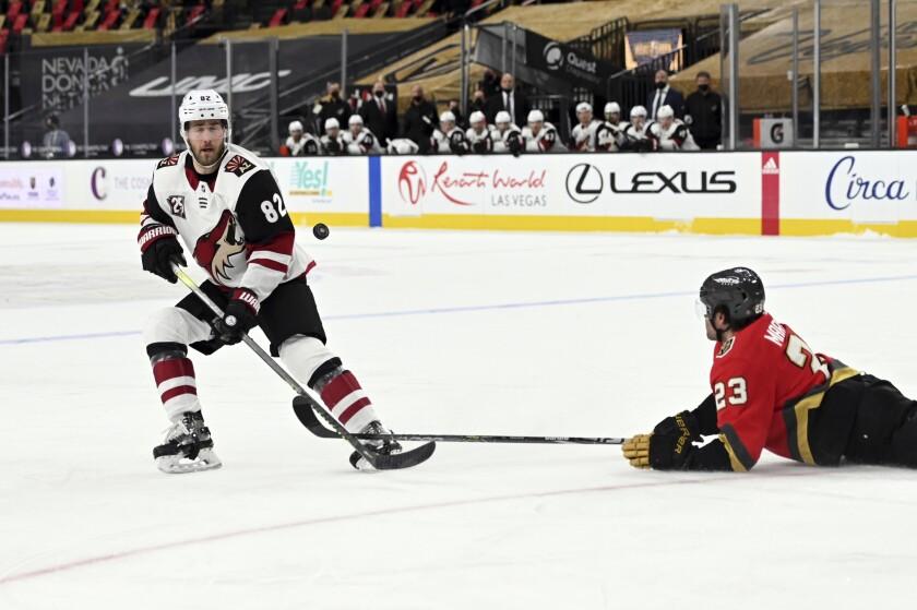Arizona Coyotes defenseman Jordan Oesterle (82) and Vegas Golden Knights defenseman Alec Martinez (23) vie for the puck during the third period of an NHL hockey game Friday, April 9, 2021, in Las Vegas. (AP Photo/David Becker)