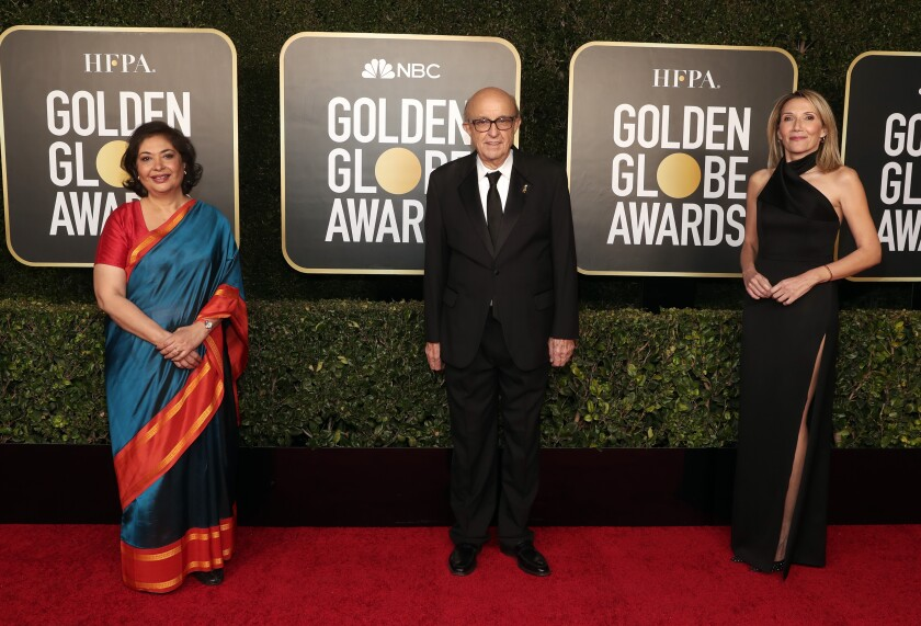 HFPA members stand on the red carpet.