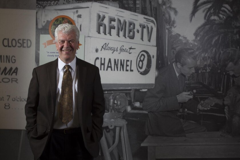 """Bill Lawrence is the newest executive member of the San Diego History Center. He is shown with the museum's exhibit honoring the 100th anniversary of the San Diego Zoo. In the background is a photo of the KFMB-TV crew filming the first """"Zoorama,"""" the first internationally syndicated TV show created in San Diego."""