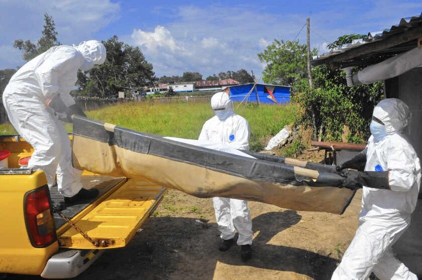 Health workers carry the body of a suspected Ebola victim from his home on the outskirts of Monrovia, Liberia.