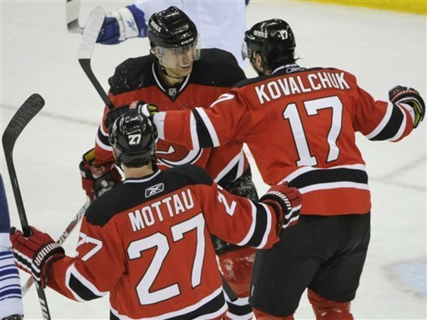 New Jersey Devils' Ilya Kovalchuk (17), of Russia and Mike Mottau (27) celebrate with Dainius Zubrus after Zubrus scored during the first period of an NHL hockey game against the Toronto Maple Leafs Friday, Feb. 5, 2010 in Newark, N.J. (AP Photo/Bill Kostroun)
