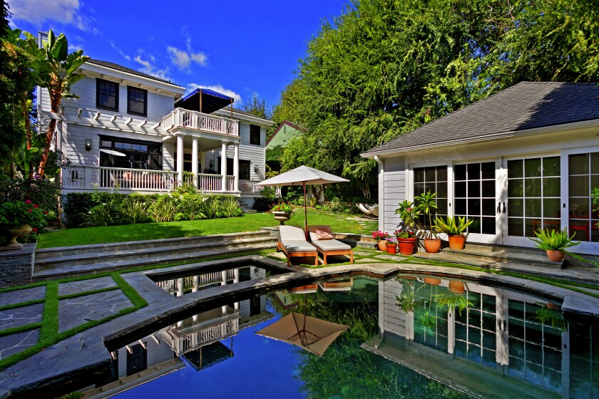 The 1920s Colonial-style home opens to a grassy yard with a pool, spa and guesthouse.