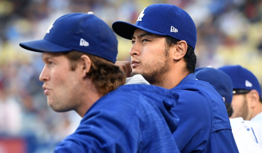 Former Dodgers pitcher Yu Darvish, right, stands next to Clayton Kershaw in the dugout at Dodger Stadium on Aug. 15, 2017.