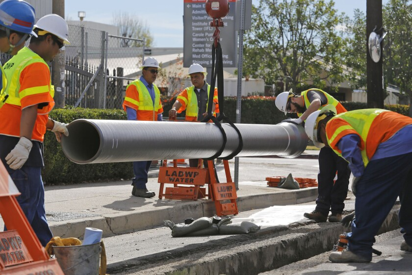 DWP workers install a rubber gasket into a quake-resistant ductile pipe in January in the Northridge area.