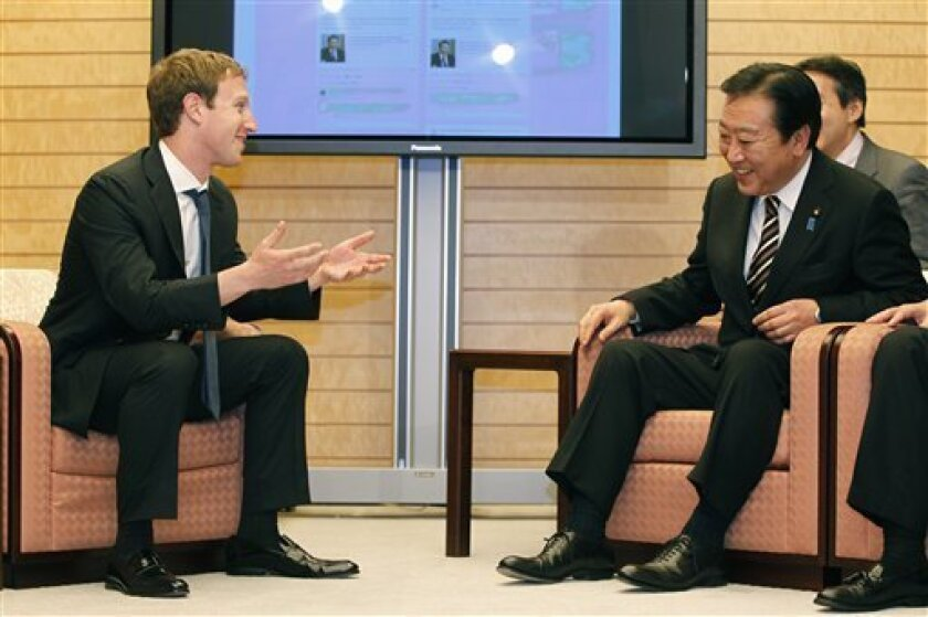 Facebook CEO Mark Zuckerberg, left, talks with Japan's Prime Minister Yoshihiko Noda in front of a monitor displaying a facebook page of Prime Minister's Office of Japan as they meet at the latter's official residence in Tokyo Thursday, March 29, 2012. Zuckerberg said Japan's tsunami has inspired him to seek more ways for his ubiquitous social media platform to help people hit by natural disasters. Zuckerberg told Noda that he believes Facebook can be used to keep people in disasters in touch with each other and provide crucial information in a time of crisis. (AP Photo/Yuriko Nakao, Pool)