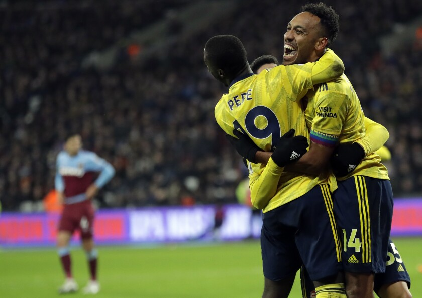 Arsenal's Pierre-Emerick Aubameyang, right, celebrates with teammates after scoring his side's third goal duels for the ball with during the English Premier League soccer match between West Ham Utd and Arsenal at the London Stadium in London, Monday, Dec. 9, 2019. (AP Photo/Kirsty Wigglesworth)