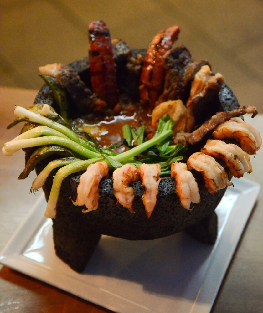 Molcajete Cielo, Mar y Tierra consists of cactus paddles, shrimp, rib eye and ranch-style chorizo draped over the sides of a hot stone mortar.