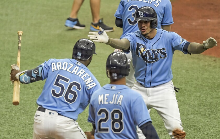 Tampa Bay Rays' Randy Arozarena (56) and Francisco Mejia (28) congratulate Willy Adames after his two-run home run off New York Mets' Marcus Stroman during the fifth inning of a baseball game Sunday, May 16, 2021, in St. Petersburg, Fla. (AP Photo/Steve Nesius)