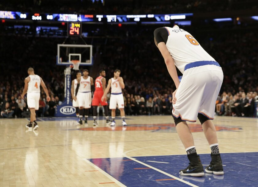 New York Knicks' Kristaps Porzingis, right, reacts after injuring his foot during the second half of the NBA basketball game against the Philadelphia 76ers, Monday, Jan. 18, 2016 in New York. The Knicks defeated the 76ers in double overtime 119-113.(AP Photo/Seth Wenig)