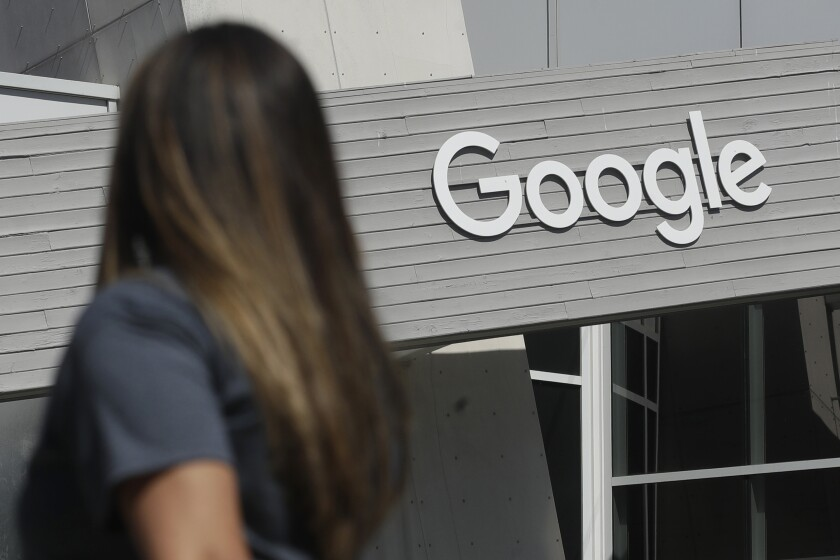 FILE - In this Sept. 24, 2019, file photo a woman walks below a Google sign on the campus in Mountain View, Calif. Google employees are demanding the company issue a climate plan that commits to zero emissions by 2030. More than 1,000 workers are signed the petition posted online Monday, Nov. 4. (AP Photo/Jeff Chiu, File)