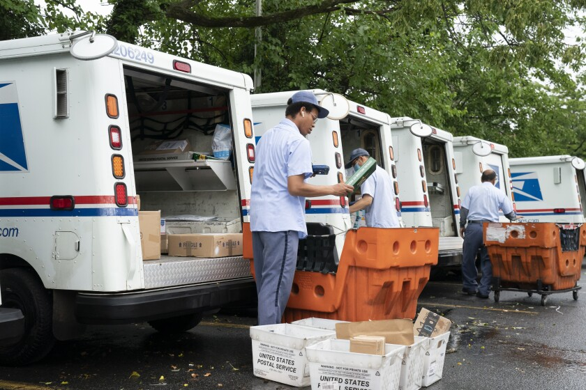 Letter carriers load mail trucks for deliveries in July at a U.S. Postal Service facility in McLean, Va.