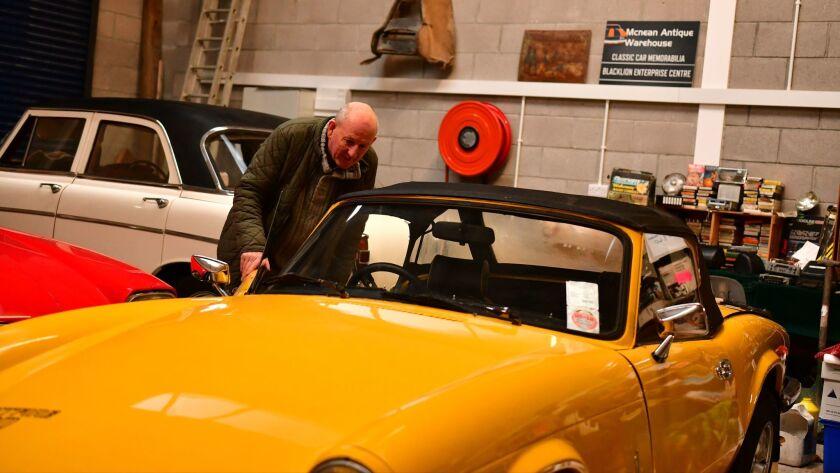 Hughie Nolan inspecting a 1970s vintage Jaguar sportscar for sale at his antique shop in Blacklion,