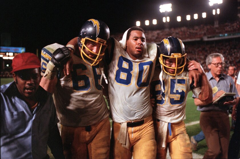 In what's become a classic sports photo, a depleted Kellen Winslow (80) is helped off the field by teammates in the Chargers' memorable playoff defeat of the Miami Dolphins in the Orange Bowl on Jan. 2, 1982. Photo by BOB IVINS