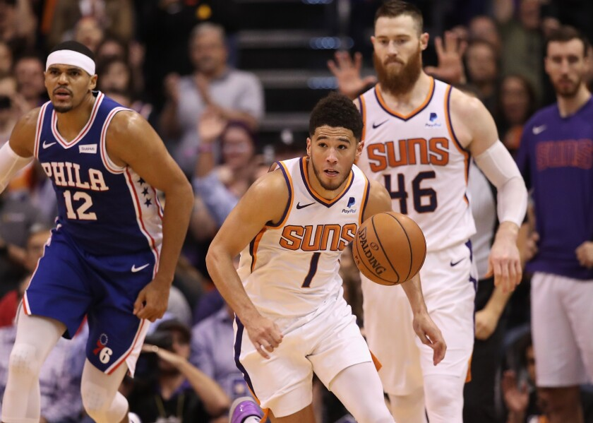 Suns guard Devin Booker starts a fastbreak ahead of teammate Aron Baynes and 76ers forward Tobias Harris during a 114-109 win on Nov. 4, 2019, in Phoenix.