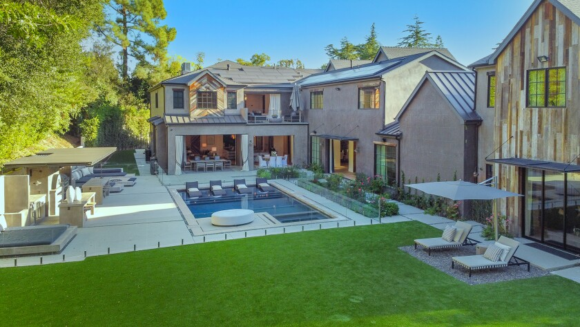 A compound with a pool and big yard.