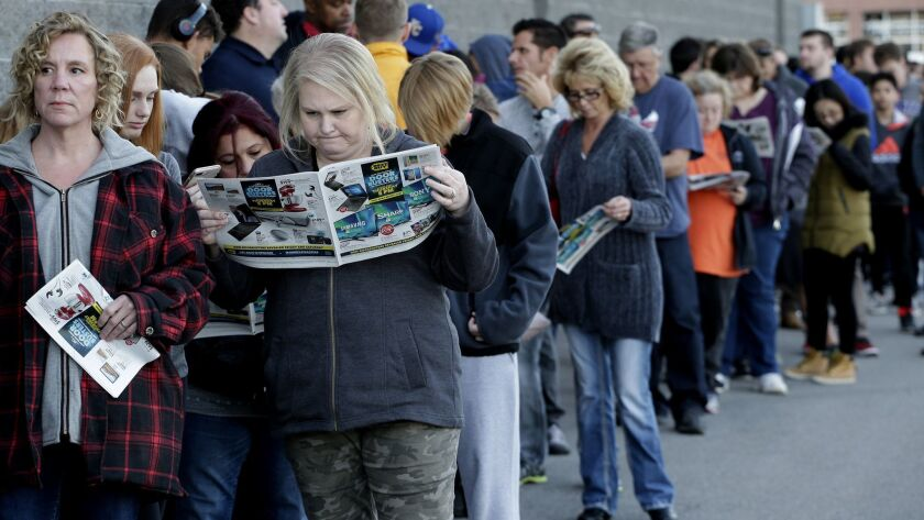 FILE - In this Nov. 23, 2017, file photo, people wait in line for a Best Buy store to open for a Bla