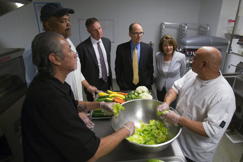 Labor Secretary Thomas Perez, center, spoke with veterans left-to-right Mario Moreno (Marines) Kevin Greene (Army ) and Manuel Sanchez (Navy). All three veterans work in the kitchen of the Connections Housing for veterans in downtown San Diego. Accompanying the secretary were Reps Scott Peters and Susan Davis.