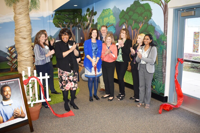 Ginger Couvrette, Candy Carson, Principal Gail West, T.J. Zane, Katie MacLeod, Michelle O'Connor-Ratcliff, Jennifer Burks and Darshana Patel cut the ribbon for the new reading room.