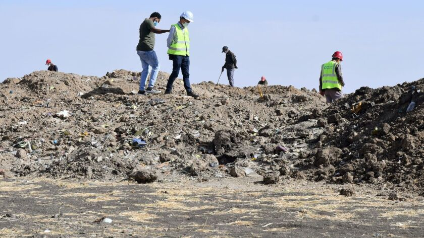 Rescue workers search the site for pieces of the wreckage of an Ethiopia Airlines Boeing 737 Max 8 aircraft near Bishoftu, Ethiopia, on March 13.