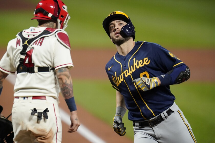 Milwaukee Brewers' Ryan Braun, right, scores past St. Louis Cardinals catcher Yadier Molina after hitting a solo home run during the fourth inning of a baseball game Saturday, Sept. 26, 2020, in St. Louis. (AP Photo/Jeff Roberson)