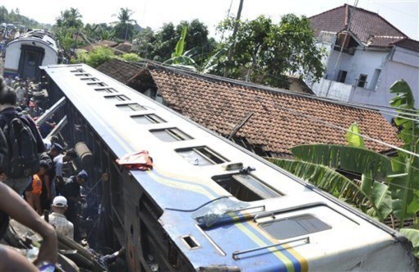 Rescuers search for victims of a train crash near a station in Petarukan in Central Java, Indonesia, Saturday, Oct. 2, 2010. The early morning train crash killed dozens of people and injured another dozens, many of them critically, officials and witnesses said. (AP Photo)