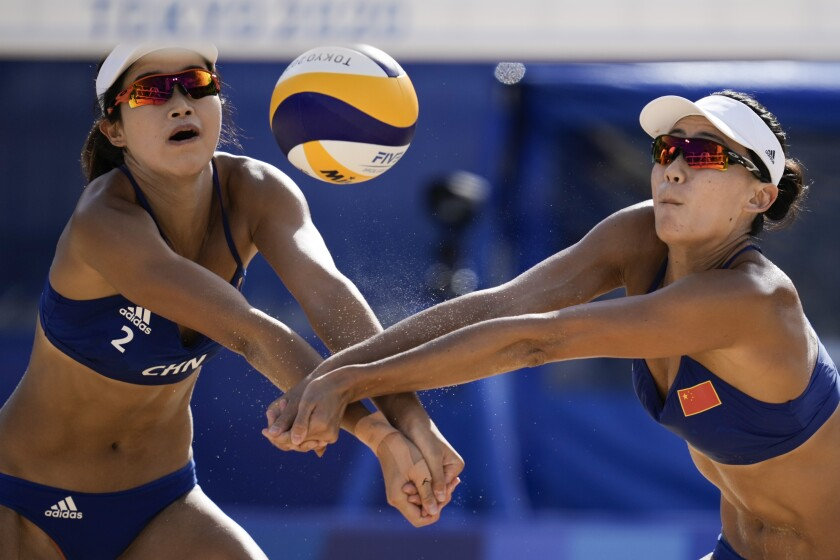 Xue Chen, right, of China, and teammate Wang Zinzin, close in on the ball during a women's beach volleyball match against the Netherlands at the 2020 Summer Olympics, Tuesday, July 27, 2021, in Tokyo, Japan. (AP Photo/Felipe Dana)