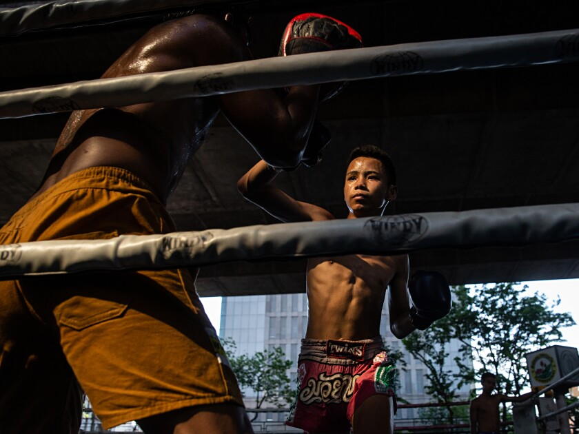 Pheearanut Saleephol, 14, spars against his trainer, Jamlong Jaipakdee,50, at the Sor. Pullsawas Gym in Bangkok, Thailand on Monday April 8, 2019. Thai Boxing, locally known as Muay Thai, is considered to be the national sport of Thailand, with children as young as 8 years old competing professionally. In recent years, allowing children under the age of 15 to compete has become controversial due to potential health risks. Pheearanut has been boxing since age 12. His adoptive father and grandfather boxed professionally in their youth and he decided to follow in their footsteps. Photo by Lauren DeCicca