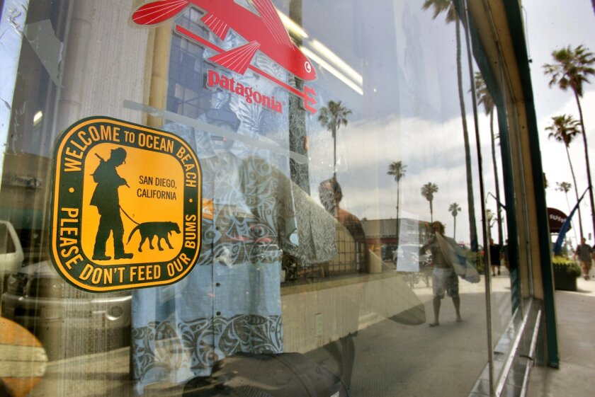A sticker at the South Coast Longboards surf shop in Ocean Beach urges people not to feed the homeless. Aimed to thwart what some call aggressive panhandling, the stickers have sparked controversy.