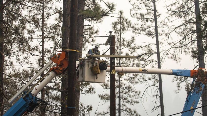 CONCOW, CALIF. - NOVEMBER 16: Crews of PG&E work to reinstall utility poles along Hoffman road on Fr