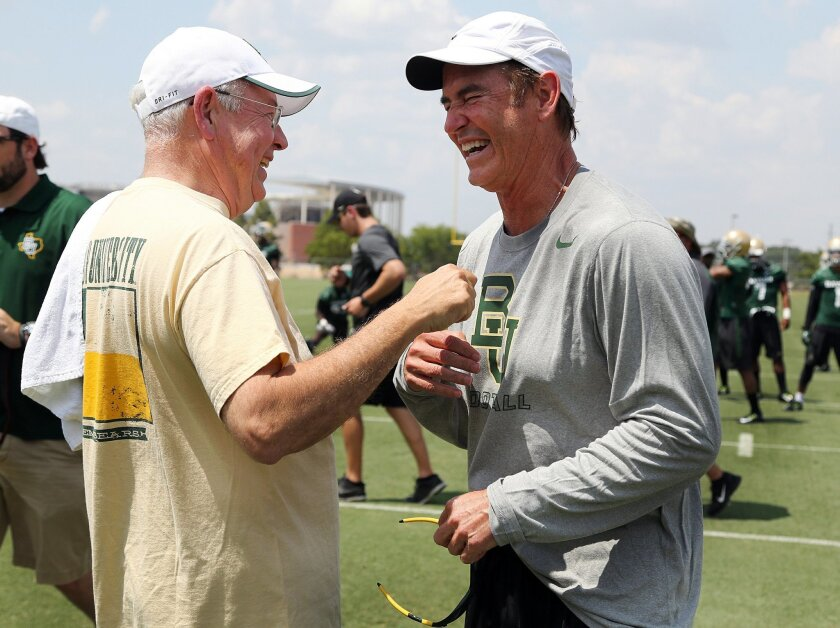 FILE - In this Aug. 5, 2014, file photo,Baylor University President Ken Starr, left, jokes with head football coach Art Briles, right, on the first day of NCAA college football practice in Waco, Texas. Baylor University's board of regents says it will fire Briles and re-assign Starr in response to