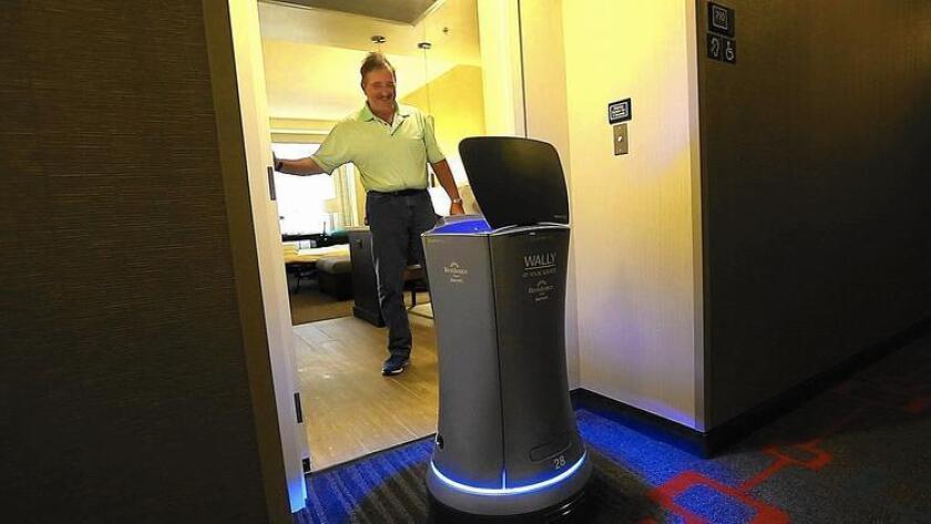 William Savoie, de Burlington (Vermont), le abre la puerta a Wally, un botones robot, que le entrega su orden de dos botellas de agua en su habitación del Residence Inn by Marriott, en el Century Boulevard de Los Ángeles. El robot puede entregar cosas pequeñas como toallas, bocadillos y café a huéspedes del hotel.