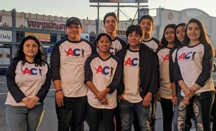 """Youth from the Advocates for Change Today group pose near a """"Escape the Vape"""" billboard in City Heights."""