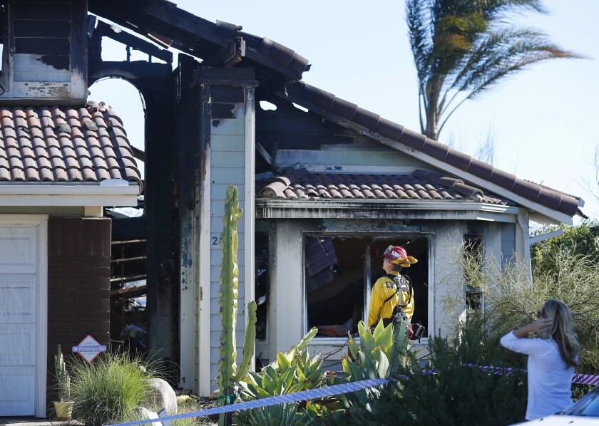 San Miguel fire Capt. Bob Lundstrom looked over a home on Wind River Road in Rancho San Diego that was gutted by the fire.