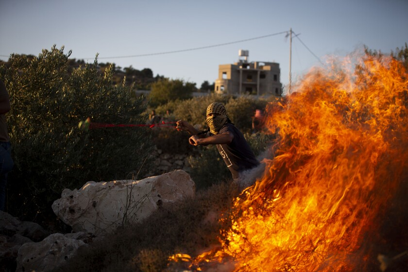 A Palestinian protester uses slingshot to hurls stones during protest against the West Bank Jewish settlement outpost of Eviatar that was rapidly established last month, at the Palestinian village of Beita, near the West Bank city of Nablus, Thursday, June 24, 2021. The Palestinians say it was established on their farmland and fear it will grow and merge with other large settlements in the area. (AP Photo/Majdi Mohammed)